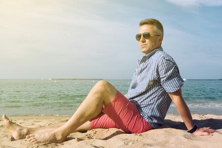 L'homme prend un bain de soleil sur la côte de la mer, la nature de l'été en plein air. Portrait de bel homme d'âge moyen repose sur la plage, l'image tonique.
