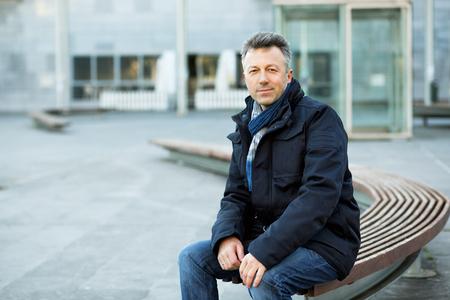hombres maduros: Hombre guapo. Retrato al aire libre del varón europeo del invierno. Atractivo confía en hombre de mediana edad, retrato de la ciudad, imagen tonificada y el ruido añadido.
