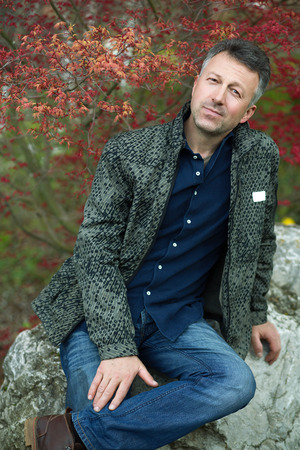 manful: Portrait of handsome man posing in spring Japanese garden. Outdoor male portrait over stones and red tree.