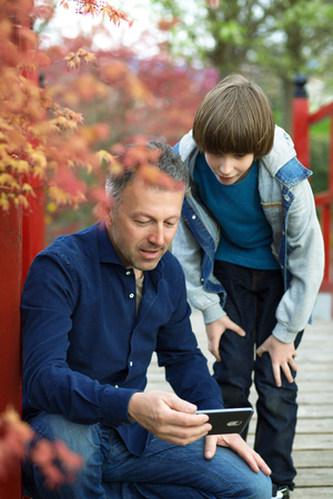 Father with teen son using smart phone outdoor together. Young boy with his father in spring park. Stock Photo
