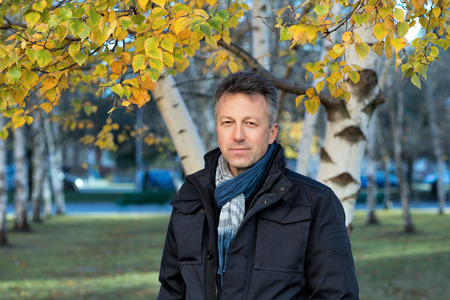 manful: Handsome happy smiling man. Outdoor autumn male portrait. Attractive confident middle-aged man posing in city park, birch grove.