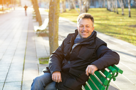 Handsome happy smiling man. Outdoor winter european male portrait. Attractive confident middle-aged man resting on bench in city park, image toned. Stock Photo
