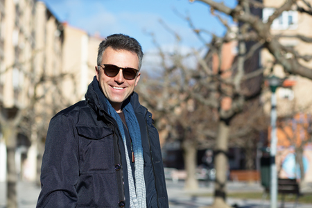 manful: Handsome happy smiling man. Outdoor winter male portrait. Attractive confident middle-aged man in sunglasses walking in city. Stock Photo