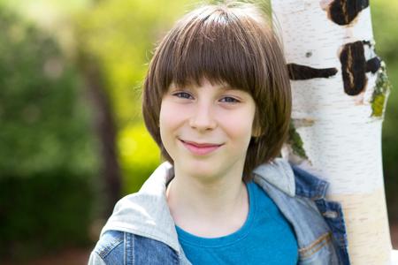 Retrato de chico guapo al aire libre. Niño adolescente neer el abedul en el parque de primavera