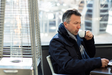 manful: Handsome man in street winter cafe drinking coffe and wine. Male portrait. Attractive confident middle-aged man sitting in city bar, image toned, image toned and noise added. Stock Photo