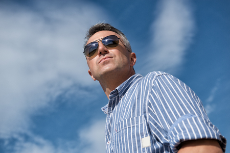 manful: Handsome man. Outdoor male portrait. Middle-aged man, summer outdoor portrait over sky, image toned. Stock Photo