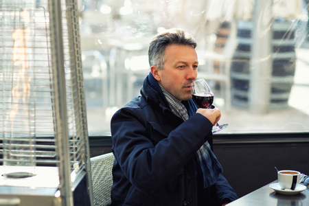 manful: Handsome man in street winter cafe drinking coffe and wine. Male portrait. Attractive confident middle-aged man sitting in city bar, image toned, image toned. Stock Photo