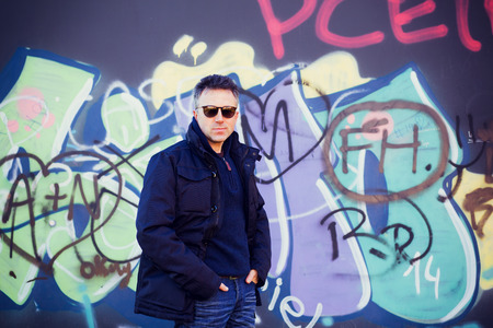 manful: Handsome happy smiling man. Outdoor winter male portrait. Attractive confident middle-aged man in sunglasses posing in city park over grunge abstract art graffiti wall, image toned and noise added.