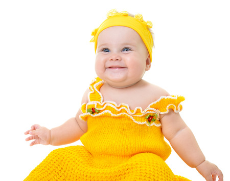 Adorable baby girl posing and happy smiling in studio in yellow dress, short over white background. Portrait of cute child. Beautiful little girl.