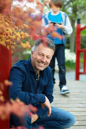 manful: Portrait of handsome happy smiling man posing in spring Japanese garden with his son using smartphone ion background Stock Photo