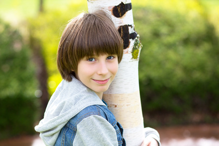 Outdoor handsome boys portrait. Teen boy embracing the birch in spring park Stock Photo