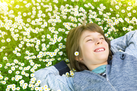 Handsome happy smiling young boy lying on summer meadow green grass with daisy. Attractive smiling teen boy posing over nature background, image toned. Stock Photo
