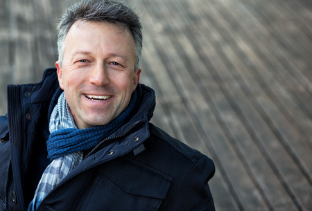 manful: Handsome happy smiling man. Outdoor winter european male portrait. Attractive confident middle-aged man, city portrait, image toned and noise added. Stock Photo