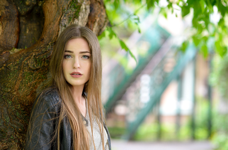 doldrums: Young attractive woman hiding from the rain under a tree. Girl in rainy day, soft focus. Beautiful female face.