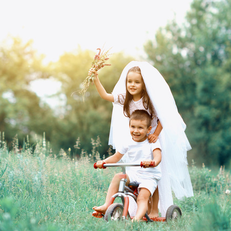 Young bride and groom playing wedding summer outdoor. Children like newlyweds on bicycle. Bridal, wedding concept, image toned and noise added. Stock Photo