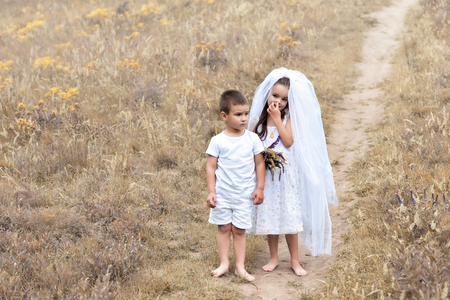 whote: Young bride and groom playing wedding summer outdoor. Children like newlyweds. Little girl in bride whote dress and bridal veil kissing her little boy groom, kids game. Bridal, wedding concept, image toned and noise added. Stock Photo