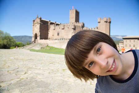 Young boy posing and smiling over ancient spanish castle Javier, Navarre, Spain. Cultural and historical spanish heritage. Young tourist agains architectural sight