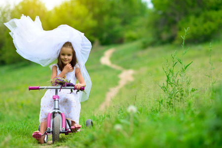 Young bride playing wedding summer outdoor, newlyweds. Little girl in bride white dress and bridal veil posing over fresh greenery on bicycle, kids game. Bridal, wedding concept, image toned and noise added.