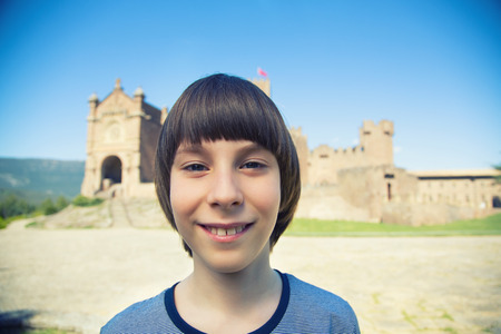 Beautiful 11 years old boy posing and smiling over ancient spanish castle Javier, Navarre, Spain. Cultural and historical spanish heritage. Young tourist making selfie agains architectural sight, wide angle, image toned