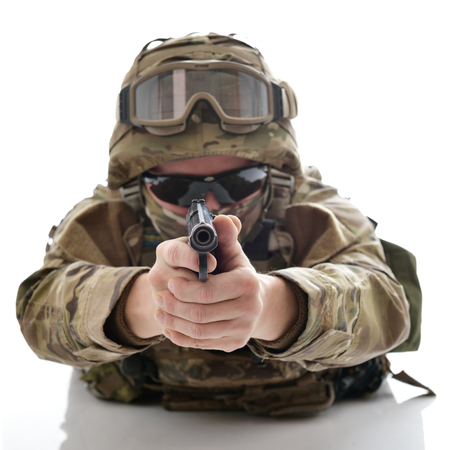 Military man in camouflage uniform, armor vest, dark glasses and helmet with gun aiming at the enemy, isolated on white background Stock Photo