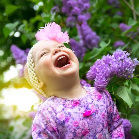 Beautiful little girl playing in spring park, lilac flowers garden. Childhood. Cute kids face over nature background. Cheerful childs portrait, soft focus.