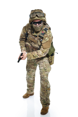 Military man in camouflage uniform, armor vest, dark glasses and helmet with gun aiming at the enemy Stock Photo