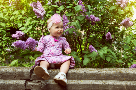 sanguine: Beautiful little girl appy smiling and smells lilac flowers in spring park. Childhood. Cute kids face over nature background. Cheerful childs portrait, soft focus, image toned