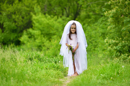 Young bride  playing wedding summer outdoor, newlyweds. Little girl in bride white dress and bridal veil posing over fresh greenery, kids game. Bridal, wedding concept Stock Photo