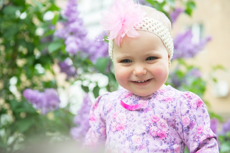 Beautiful little girl happy smiling over lilac flowers in spring park. Childhood. Cute kids face over nature background. Cheerful childs portrait, soft focus.