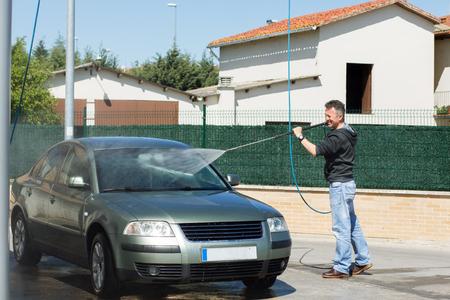 車は洗う。男は屋外ブラシと高圧水洗浄車 写真素材 - 80870056
