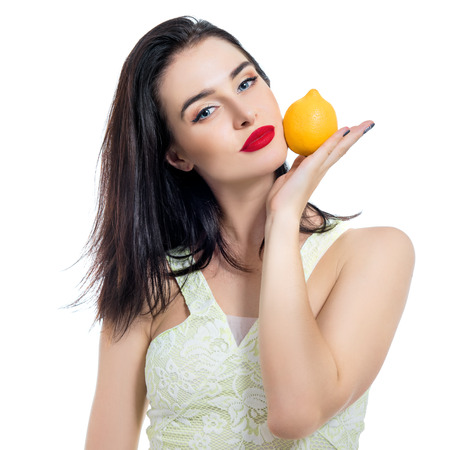 nourishing: Excited beautiful girl holding lemon and posing in studio over white background.