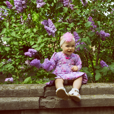 Beautiful little girl appy smiling and smells lilac flowers in spring park. Childhood. Cute kids face over nature background. Cheerful childs portrait, soft focus, image toned and noise added