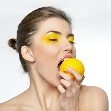 feminity: Young attractive girl posing at studio with lemon. Beautiful female face with healthy skin and close eyes. Young woman with vivid makeup eats lemon. Stock Photo