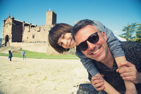 Padre e hijo posando y sonriendo sobre el antiguo castillo español Javier, Navarra, España. Mirada familiar sobre el patrimonio cultural e histórico español. Joven turista haciendo selfie contra vista arquitectónica, gran angular, imagen en tonos Foto de archivo