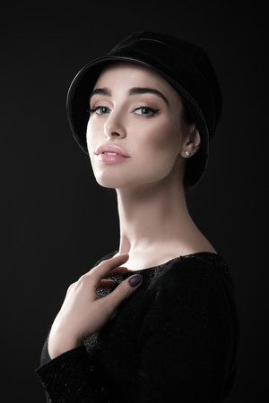 Fashion woman. Black and white portrait of beautiful young elegant lady in black dress and hat. Vintage styling. Beauty, fashion, style. Image toned photo