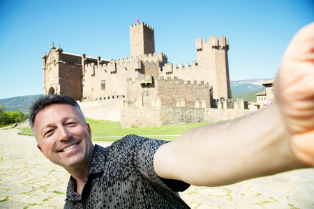 Happy smiling man making selfie over ancient spanish castle Javier, Navarre, Spain. Cultural and historical spanish heritage, architectural sight, wide angle, image toned Stock Photo