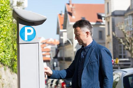 Man using parking meter, Biarritz, France. Man pays for Parking Stock Photo