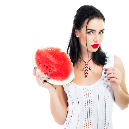 Beautiful young woman holding and eating slice of ripe red fresh juicy tasty sweet watermelon over white wall photo