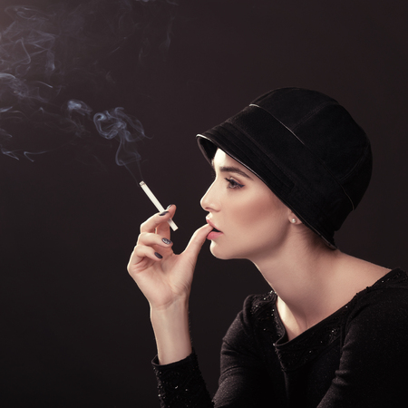 Young fashion woman smoking cigarette in hat and black drees over dark background. Vintage female portrait, styling. Image toned. photo