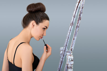 aged: Portrait of beautiful woman holding lipstick and looking at mirror, profile. silhouette of attractive girl in studio over blue-gray background with copy space.