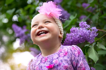 sanguine: Beautiful little girl happy smiling outdoor in spring park over lilac flowers backgrond. Real genuine emotions. Childhood. Cute kids face. Cheerful childs portrait, soft focus.