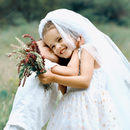 whote: Young bride and groom playing wedding summer outdoor. Children like newlyweds. Little girl in bride whote dress and bridal veil kissing her little boy groom, kids game. Bridal, wedding concept.