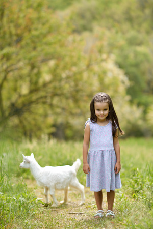 Little girl plays and huhs goatling in country, spring or summer nature outdoor. Cute kid with baby animal, countryside outdoor portrait, forest, trod, glade background. Friendship of child and yeanling, image toned. Stock Photo