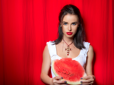 Beautiful young woman holding and eating slice of ripe red fresh juicy tasty sweet watermelon over red theatrical scenes photo