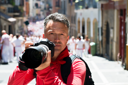 Photographer on San Fermin. Photojournalist. People celebrate San Fermin festival in traditional white and red clothing with red necktie