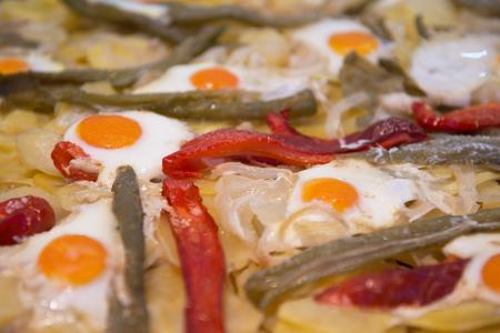 scrambled: Street food in San Fermin feast, Pamlona, Navarra, Spain. Fried eggs. Scrambled eggs with vegetables. Spanish traditional cuisine. Spanish national dish.