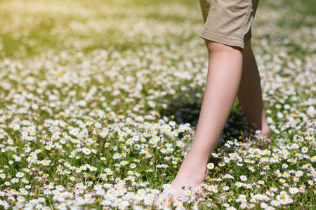 Childs feet in daisy closeup view. Shoeless boy walking on spring meadow. Little boy lying on summer meadow green grass with daisy.