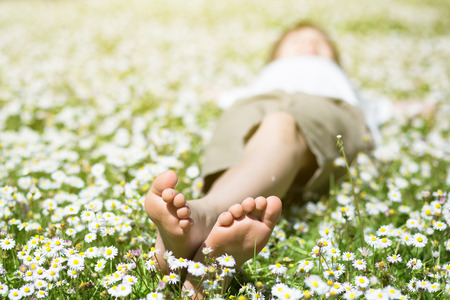 Child's feet in daisy closeup view. Shoeless boy. Little boy lying on summer meadow green grass with daisy. Stock Photo