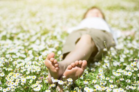 Child's feet in daisy closeup view. Shoeless boy. Little boy lying on summer meadow green grass with daisy. Standard-Bild