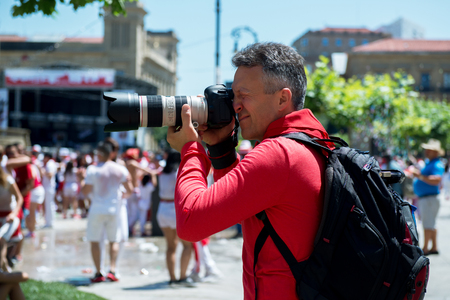 hemingway: Photographer on San Fermin. Photojournalist. People celebrate San Fermin festival in traditional white and red clothing with red necktie, 06 July 2016, Pamplona, Navarra, Spain.